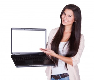 Beautiful charming woman holding a laptop facing the camera with a blank white screen for your text or advertising