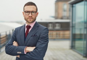 Confident stylish businessman wearing glasses standing on an open-air balcony looking thoughtfully at the camera with folded arms