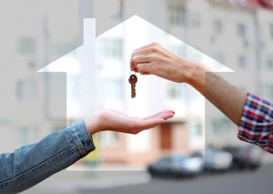 Male and female hands with keys surrounded by form of house